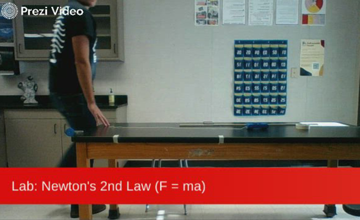 High school physics teacher William Rasor models a lab focused on Newton's 2nd Law and directs his students to collect the data and graph their findings.